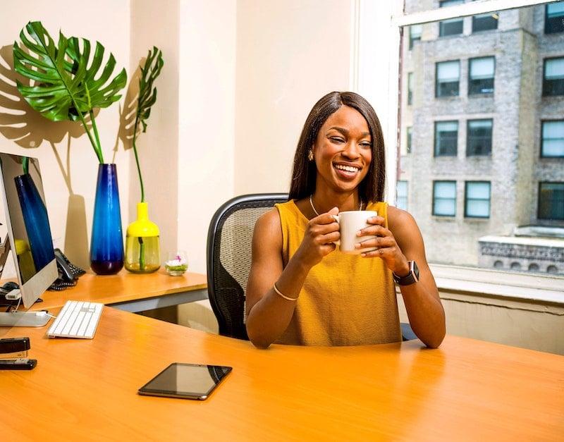 woman-holding-white-ceramic-mug-at-desk-2422287-1
